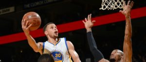 Stephen Curry sobe para a cesta marcado por David West